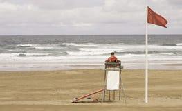 Un bagnino che si siede sulla torre di sorveglianza, parte anteriore del mare fotografia stock