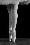 Un bailarín de ballet que se coloca en los dedos del pie mientras que baila en fondo negro Fotografía de archivo libre de regalías