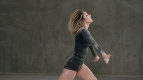 Un bailarín se vistió en cuerpo negro que el traje realiza una danza moderna en una nube del polvo o del humo blanco contra un fo almacen de video