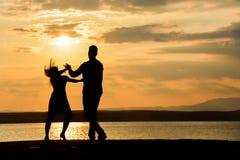 Un baile de los pares por el mar en la puesta del sol foto de archivo