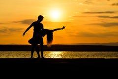 Un baile de los pares por el mar en la puesta del sol foto de archivo libre de regalías