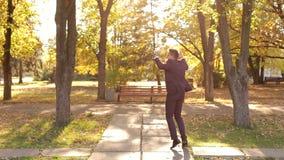 Un baile feliz acertado del hombre de negocios en el parque del otoño que disfruta de éxito almacen de metraje de vídeo
