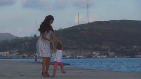 Un baile hermoso de la chica joven con el bebé en la costa al lado del mar almacen de metraje de vídeo