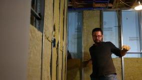Un baile torpe del contratista en un sitio de trabajo en el sótano inacabado almacen de video