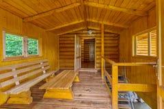 Un bain de vapeur en bois, avec de petites fenêtres, une table et un banc Image stock