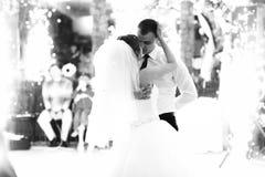 Un baiser tendre des nouveaux mariés dans les lumières des feux d'artifice Photographie stock