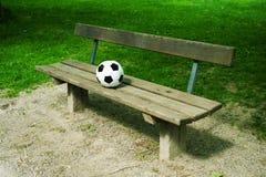Un balón de fútbol en un banco de parque imagenes de archivo