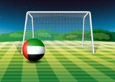 Un balón de fútbol en el campo con la bandera de los UAE Fotografía de archivo libre de regalías