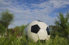 Un balón de fútbol en la hierba contra el cielo Imágenes de archivo libres de regalías