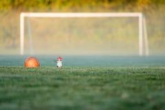 Un balón de fútbol y una botella de agua delante de una meta del fútbol Fotografía de archivo