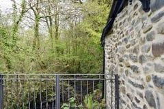 Un balacony allegato ad una costruzione sviluppata di pietra sopra lo sguardo del terreno boscoso, là è molto ` s dell'albero e f immagine stock