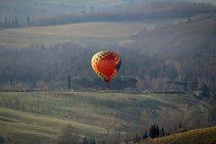 Un ballon à air chaud au lever de soleil au-dessus des collines de chianti en Toscane photos libres de droits