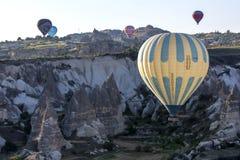 Un ballon à air chaud vole en bas de la vallée d'amour au lever de soleil près de Goreme dans la région de Cappadocia de la Turqu Image libre de droits