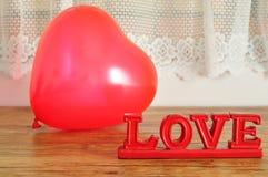 Un ballon rouge de forme de coeur avec l'amour de mot Photographie stock libre de droits