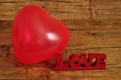 Un ballon rouge de forme de coeur avec l'amour de mot Image stock