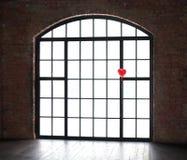 Un ballon sous forme de coeur rouge sur un fond de fenêtre Photographie stock libre de droits