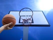 Un baloncesto del juego del hombre Opinión de ángulo bajo del aro de baloncesto contra el cielo azul fotografía de archivo