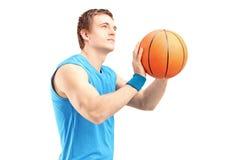 Un baloncesto joven del tiroteo del jugador de básquet Fotos de archivo libres de regalías