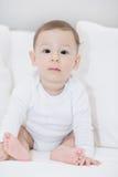 Un bambino adorabile e felice che esamina macchina fotografica sui cuscini bianchi Fotografia Stock