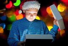 Un bambino apre una casella con un regalo Immagini Stock Libere da Diritti
