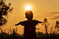 Un bambino asiatico che gioca nel campo, si sente libero e vuole volare per libertà Immagine Stock