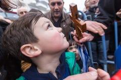 Un bambino bacia un incrocio di legno recuperato dal mare durante Immagini Stock Libere da Diritti