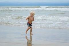 Un bambino biondo felice del ragazzo che cammina in acqua ad una spiaggia della riva di mare, Nha Trang, Vietnam Immagini Stock Libere da Diritti
