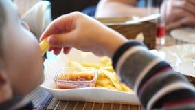 Un bambino in un caffè degli alimenti a rapida preparazione che mangia le patate fritte in un piatto Alto vicino della mano Fette video d archivio