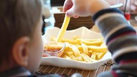 Un bambino in un caffè degli alimenti a rapida preparazione che mangia le patate fritte in un piatto Alto vicino della mano Fette stock footage