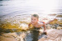 Un bambino caucasico di tre anni in costume da bagno rosso si trova sul suo stomaco nell'acqua vicino alla sponda del fiume di un Fotografie Stock