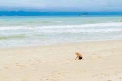 Un bambino che attinge la sabbia al bech da solo, il Vietnam, Nha-trang fotografie stock