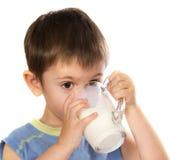 Un bambino che beve un certo latte Immagini Stock Libere da Diritti