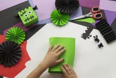 Un bambino che fa un decoro di Frankenstein di Halloween dalla carta colorata Fotografia Stock