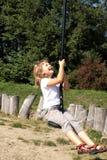 Un bambino che gioca sul campo da giuoco Fotografia Stock Libera da Diritti
