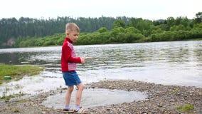 Un bambino che gioca sulle banche del fiume, il bello paesaggio di estate Ricreazione esterna archivi video