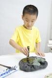 Un bambino che impara calligrafia cinese Fotografie Stock Libere da Diritti