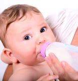 Un bambino che mangia latte dalla bottiglia immagine stock