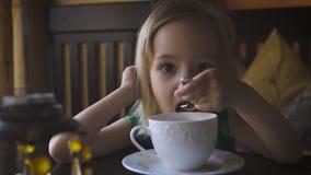 Un bambino che mangia prima colazione ad un caffè accogliente Un tè bevente della ragazza adorabile e godere della sua prima cola stock footage