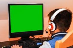 Un bambino che per mezzo del computer del desctop fotografia stock libera da diritti