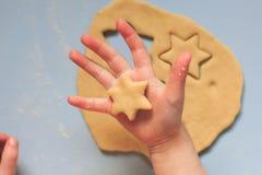 Un bambino che produce i biscotti del ritaglio con le taglierine del biscotto su una tavola blu Fotografia Stock