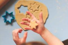 Un bambino che produce i biscotti del ritaglio con le taglierine del biscotto su una tavola blu Fotografie Stock Libere da Diritti