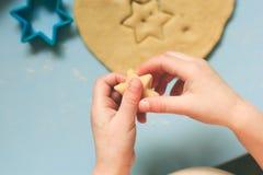 Un bambino che produce i biscotti del ritaglio con le taglierine del biscotto su una tavola blu Immagini Stock Libere da Diritti