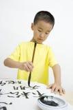 Un bambino che scrive calligrafia cinese Immagine Stock Libera da Diritti