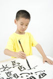Un bambino che scrive calligrafia cinese Fotografie Stock