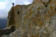 Un bambino che si arrampica su una parete della roccia del hight Fotografia Stock