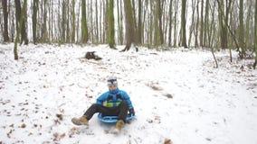 Un bambino che sledding attraverso la neve archivi video