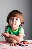 Un bambino con i pastelli e gli indicatori Fotografie Stock Libere da Diritti