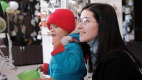 Un bambino con i punti di entusiasmo la sua mano alle merci nel deposito archivi video