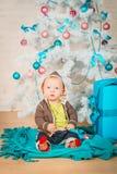 Un bambino con i regali all'albero di Natale Fotografie Stock