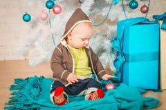 Un bambino con i regali all'albero di Natale Immagine Stock